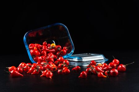 Peppers in a glass container on black background Reklamní fotografie