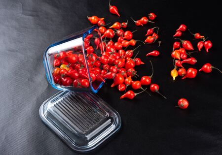 Peppers in a glass container on black background. top view