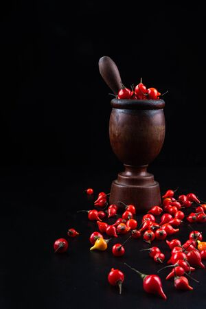 Peppers and wooden mortar on black background in selective focus.