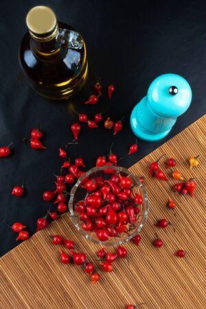 Peppers, olive oil, pepper grinder and accessories on black background. selective focus