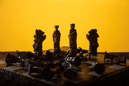 stylized chess pieces on a board with orange background and selective focus