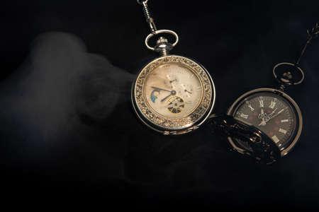 Watch vintage pocket with smoke on black background. 免版税图像