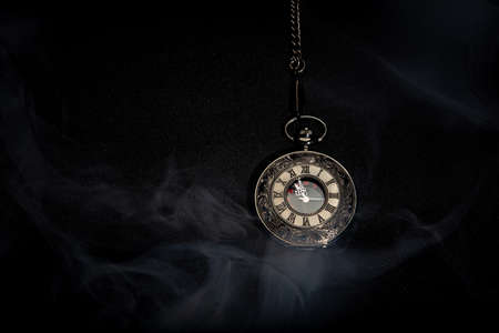 Watch vintage pocket with smoke on black background.