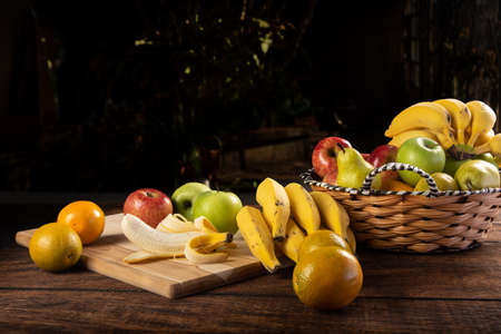 Peeled banana and apples on polished wood, placed on rustic wood with selective focus.