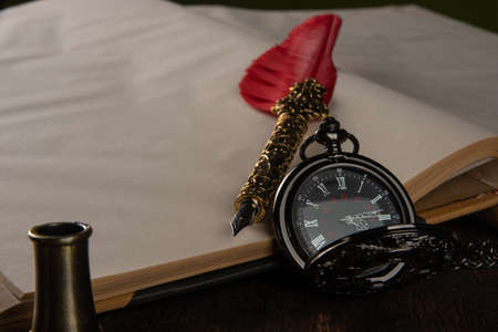 Fountain pen with red feather on a notebook and an old watch, selective focus.