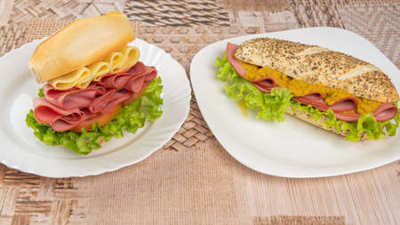 Mortadella, lettuce and cheese sandwiches and pepper and mustard sauce on white plates on a table with beige patterned tablecloth, Selective focus.