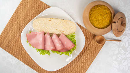Mortadella and lettuce sandwich, on a white plate and a bamboo mat and pepper sauce and mustard on a table with white towel, selective focus.