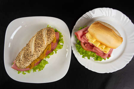 Mortadella, lettuce and cheese sandwiches and pepper and mustard sauce on white plates on a table with black towel, Top view.