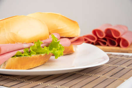 Mortadella sandwich and lettuce on a white plate on a mat and slices of mortadella next to it on a cold board on a table with white tablecloth, selective focus.
