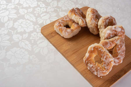 sugar-coated sweet cookies placed on a polished board on a table with white tablecloth, selective focus.
