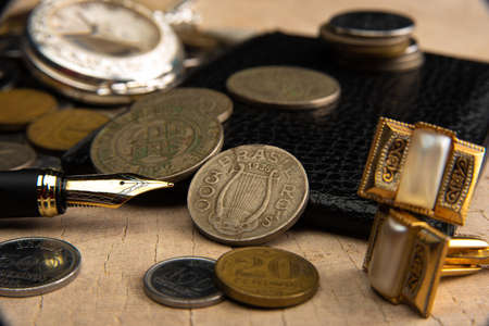 Old coins, fountain pen, wallet, cufflinks and more on a rustic wooden surface, selective focus.