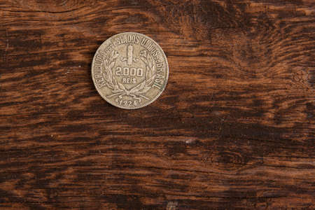 Old coins placed on a rustic wooden platform, top view.