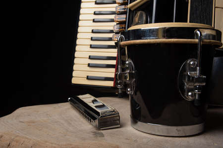 Old accordion, harmonica and bong on rustic wooden surface with black background and Low key lighting, selective focus.