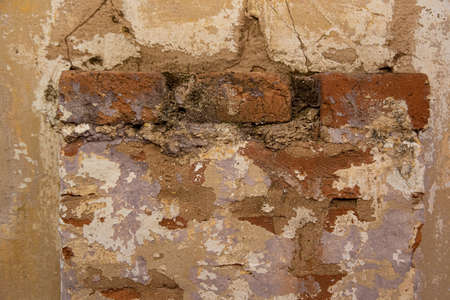 Background of an old wall with exposed bricks and old paint.