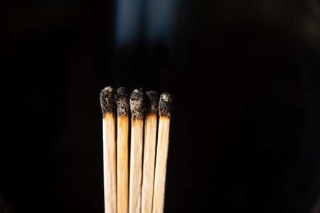 Burned phosphor sticks churning smoke on black background.