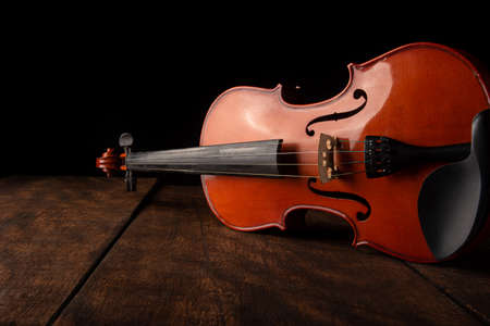 Old and beautiful violin on a rustic wooden surface and black background low key portrait, selective focus. Stock Photo