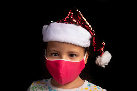 Little girl with Santa Claus hat and mask with black background, selective focus. 版權商用圖片