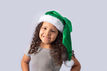 Little girl with Mrs. Claus green hat, gray gradient background, selective focus.