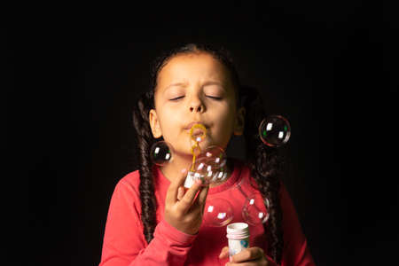 Brazilian girl with pink top playing soap bubbles, low key portrait, black background, selective focus. 免版税图像