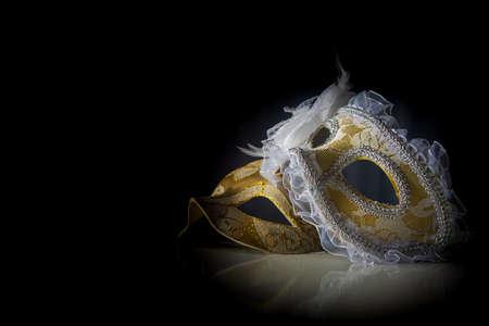 Carnival venetian masks on black surface, low key image, directed light, selective focus.