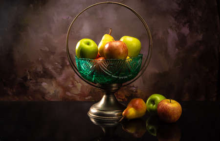 Arrangement of fruits in an old fruit bowl on black surface with spotted background, selective focus.