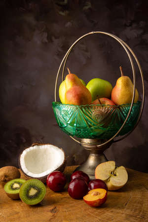 Arrangement of fruits in an old fruit bowl on rustic wood with spotted background, selective focus. Imagens