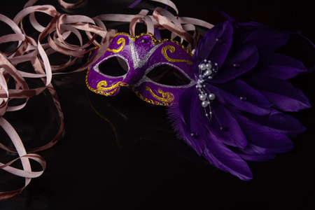 Carnival mask, lilas venetian mask on black surface with streamers, selective focus. Banque d'images