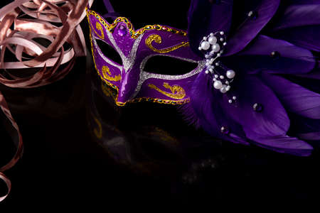 Carnival mask, lilas venetian mask on black surface with streamers, selective focus.
