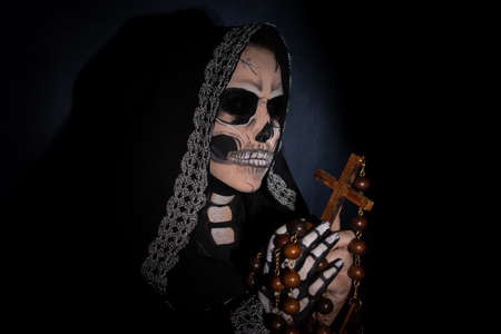 The death. Artistic makeup representing death, Low Key image, Death holding a wooden crucifix, selective focus.