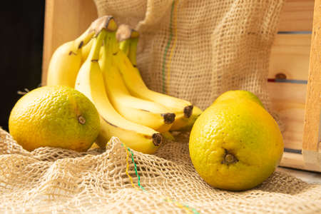Bananas and oranges, arrangement with oranges and bananas, rustic wooden box and rustic fabric, selective focus.