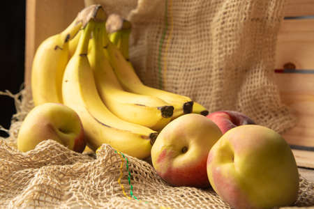 Peaches and bananas, arrangement with Peaches and bananas, rustic wooden box and rustic fabric, selective focus.