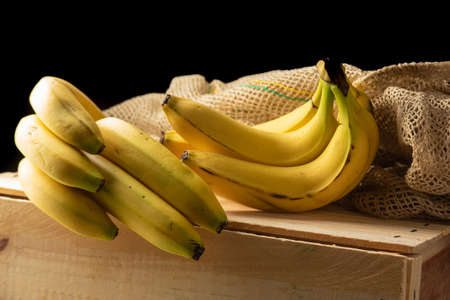 Banana, arrangement with bananas, rustic wooden box and rustic fabric, selective focus. Zdjęcie Seryjne
