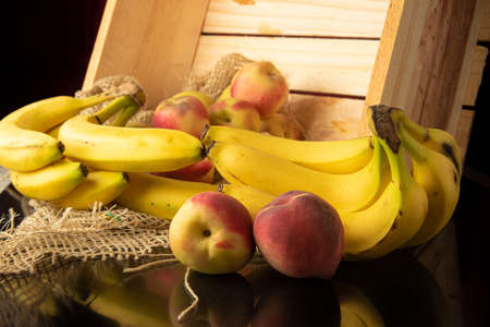 Peaches and bananas, arrangement with Peaches and bananas, rustic wooden box and rustic fabric on reflective surface, selective focus.