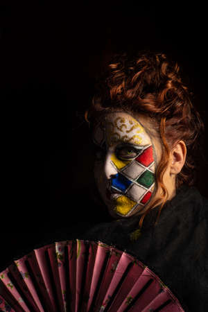 Carnival, a beautiful young woman with carnival makeup in the middle of a pandemic experiencing melancholy, black background, low key portrait, selective focus.