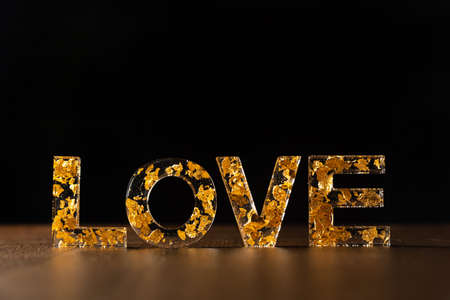 Acrylic letters with gold leaves forming the word love on wooden surface, black background, selective focus.