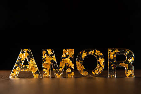 Acrylic letters with gold leaves forming the word love in portuguese on wooden surface, black background, selective focus.