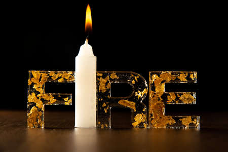 Acrylic letters with gold leaves forming the word fire with a burning candle, on wooden surface, black background, selective focus.