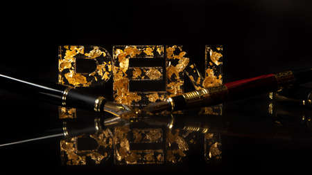 Acrylic letters with gold leaves forming the word pen and pen on reflective surface, black background, selective focus.