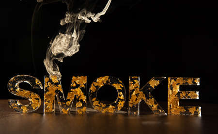 Acrylic letters with gold leaves forming the word smoke with smoke over the letters, on wooden surface, black background, selective focus.