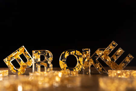 Acrylic letters with gold leaves forming the word broke on wooden surface, black background, selective focus.