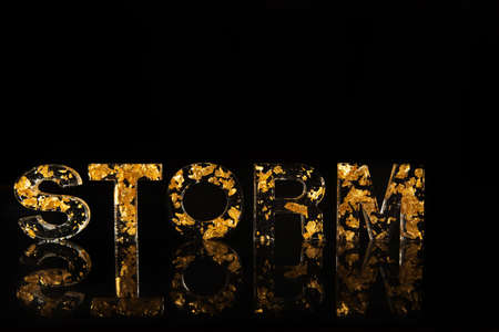 Acrylic letters with gold leaves forming the word storm on reflective surface, black background, selective focus.