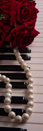 Keys of a piano with pearl necklace and bouquet of roses, selective focus.