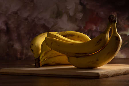 Bananas put on wood on a table, dark abstract background, directional light, selective focus.