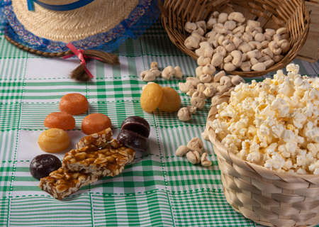 Festa junina in Brazil, typical festa junina table in brazil with popcorn and typical sweets and props, black background, selective focus.