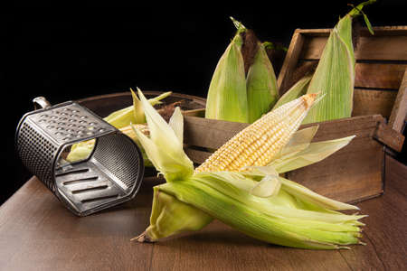 Festa Junina in Brazil, Green corn, grater and a sieve on a table, selective focus.