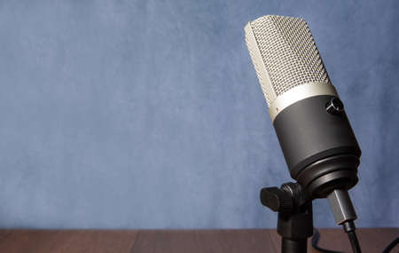 professional condenser microphone with pedestal isolated with blue stained background on wood, selective focus.
