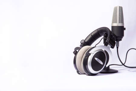 home work, professional condenser microphone and headphones on white background, high key portrait, selective focus.
