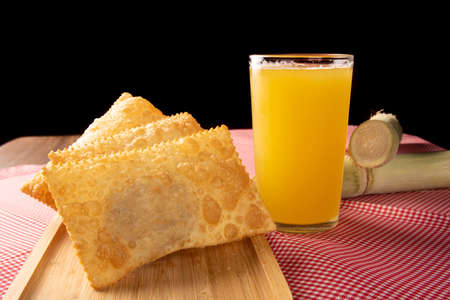 Brazilian fried pastries, a glass of sugarcane juice and canes positioned on a checkered tablecloth, black background, selective focus. Banque d'images