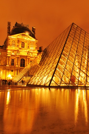 louvre pyramid: Paris, France - March, 2011: Night view of Louvre Museum with the famous glass pyramid, the main touristic attraction in Paris and one of the most visited landmarks around the world Editorial
