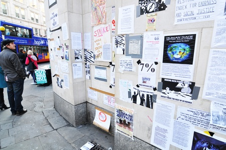 posted: London, UK - 19 Nov, 2011: People reading messages posted on Occupy London protesters wall